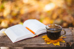 Hot coffee and red book with autumn leaves on wood. Seasonal relax concept with fallen leaves and hot drinks Royalty Free Stock Images