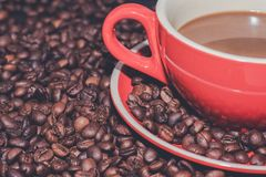 Coffee in red cup and coffee beans are the background. Hot coffee in red cup and coffee beans are the background Stock Image