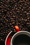 Coffee in red cup and coffee beans are the background. Royalty Free Stock Image