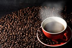 Coffee in red cup and coffee beans are the background. Stock Images