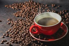 Coffee in red cup and coffee beans are the background. Stock Photos