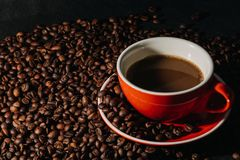 Coffee in red cup and coffee beans are the background. Hot coffee in red cup and coffee beans are the background Royalty Free Stock Photos