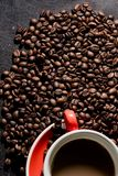 Coffee in red cup and coffee beans are the background. Hot coffee in red cup and coffee beans are the background Royalty Free Stock Image