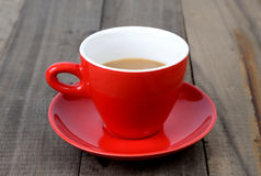 Hot coffee in red cup. Refresh yourself with a hot coffee in red cup on wooden table Royalty Free Stock Photo