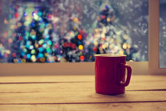 Hot coffee red cup on wood table in christmas night party. Light bokeh of christmas tree blur background with snow. vintage color tone royalty free stock photography