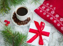 Hot coffee, red warm pullover and letter from Santa Claus on a snowy background. Hot coffee, red warm red pullover and gift with a red bow  on a snowy Royalty Free Stock Image