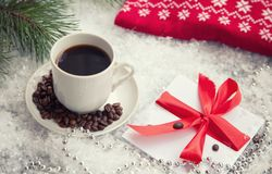 Hot coffee, red warm pullover and letter from Santa Claus on a snowy background. Hot coffee, red warm red pullover and gift with a red bow on a snowy background stock image