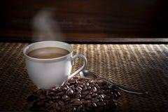 Hot coffee and roast bean on wood stock photo