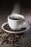 Hot coffee with smoke on brown wood. Background Royalty Free Stock Photography