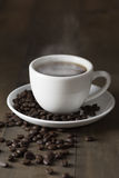 Hot coffee with smoke on brown wood. Background Royalty Free Stock Photos