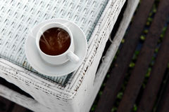 Hot coffee with smoke on white glass table. Hot coffee in white coffee cup with smoke on white glass table stock images