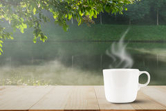 Hot coffee with steam on wooden table top on blurred misty lake and forest background Stock Photo