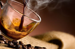 Hot coffee'steaming poured into a cup royalty free stock photography