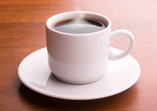 Hot coffee on a table. Dark coffee in white cup Stock Photos