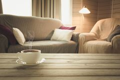 Hot coffee on tabletop in modern living room in rustic style. Blurred abstract background for design. Hot coffee on tabletop in modern living room in rustic royalty free stock image