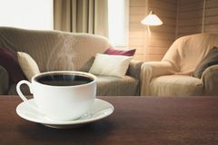 Hot coffee on tabletop in modern living room in rustic style with chair, soft divan. Hot cup of black coffee on tabletop in modern living room in rustic style royalty free stock photos