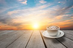 Hot coffee on top wood. Background in sunset sky Stock Photo