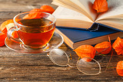 Hot coffee, vintage book, glasses and autumn leaves on wood back royalty free stock photo