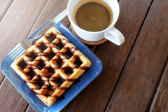 Hot coffee and Waffles with chocolate sauce on wooden table background. Have some space for write wording royalty free stock images
