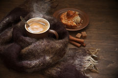 Hot coffee in warm scarf and bun Royalty Free Stock Images