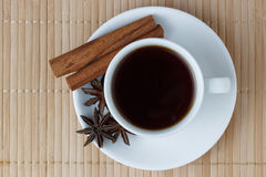 Hot coffee in a white cup with cinnamon sticks and anise.  Stock Photography
