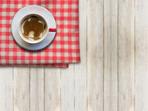 Hot coffee in white cup on red napkin on wooden table, top view. Hot coffee in white cup on red napkin on wooden table Royalty Free Stock Image
