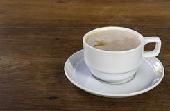 Hot coffee in white glass on wooden table stock photography