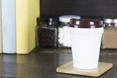 Hot coffee white plastic cup with brown cap on wooden table with Royalty Free Stock Image