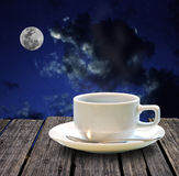 Hot coffee on wooden table at night Royalty Free Stock Photos