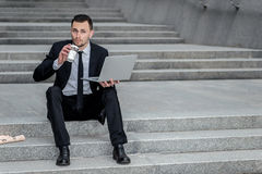 Hot coffee. Young businessman drinking coffee on the street and Stock Image