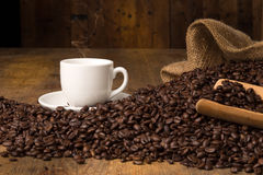 Hot coffeecup with spilled beans on table. Hot coffee cup with some roasted beans and a serving spoon on a wooden tabe Stock Images