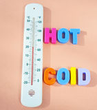 Hot and cold. Text hot and cold in colorful uppercase letters alongside a thermometer reading twenty degrees centigrade, beige background Royalty Free Stock Images