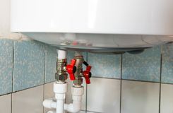 Hot and cold water taps on electric water heating boiler stock images