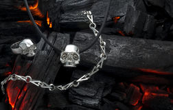 Hot collection. Jewelry made of silver for bikers and rock musicians on live coals Royalty Free Stock Photos