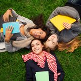 Hot college girls. Three hot college girls laying on green grass Stock Images