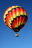 Hot Colors Hot Air Balloon. A very colorful hot air balloon soars in a clear blue sky Royalty Free Stock Images