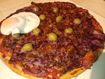 Hot cooked deep pan pizza. Covered in melted portwine Derby cheese, fried egg and olives stock image