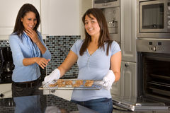 Hot cookies. Young women taking fresh baked cookies out of the oven stock images