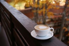 Hot cozy drink in cup on wooden railing at balcony. Space for text royalty free stock photography