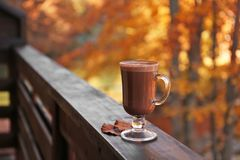 Hot cozy drink in glass cup and fallen autumn leaves on wooden railing at balcony stock photo