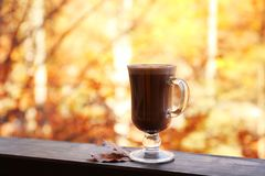 Hot cozy drink in glass cup and fallen autumn leaves on wooden railing at balcony royalty free stock images