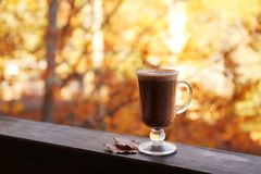 Hot cozy drink in glass cup and fallen autumn leaves on wooden railing at balcony royalty free stock photos
