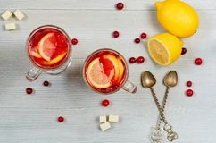 Hot cranberry tea or winter sangria with fresh lemons in glasses on the gray concrete background. Top view royalty free stock photography