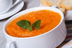 Hot cream soup of carrots close-up in white plate Stock Images