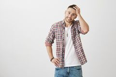 Hot creative young man with stylish glasses and haircut, smiling anxiously while touching hair, holding hand on waist. Standing over gray background. Guy Stock Photography