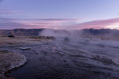 The hot creek winds its way through Owen`s Valley beneath the pastel colored Sierras stock photo