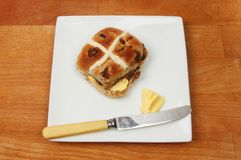 Hot cros bun on a tabletop. Hot cross bun with butter and a knife on a plate on a wooden tabletop Stock Images