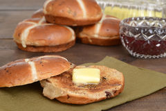 Hot cross bun with butter Royalty Free Stock Photo