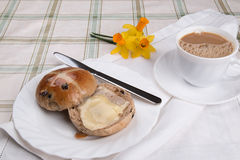 Hot cross bun cut and buttered on a white plate cup of tea napkin Royalty Free Stock Photos