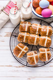 Hot cross bun on tray with Easter vibrant eggs and milk. Royalty Free Stock Photos